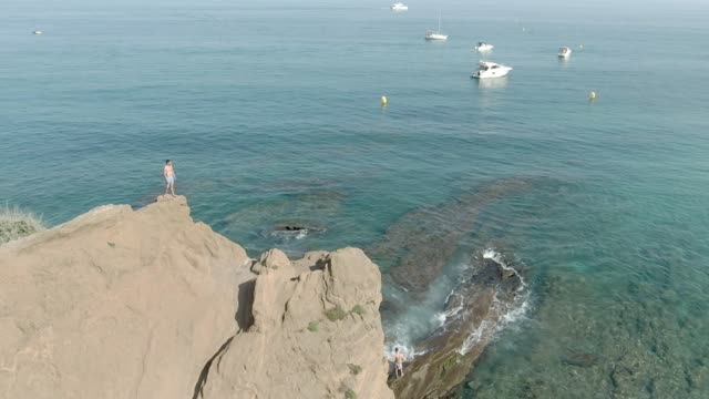 Aerial shooting of a young man standing on a cliff above a clear sea