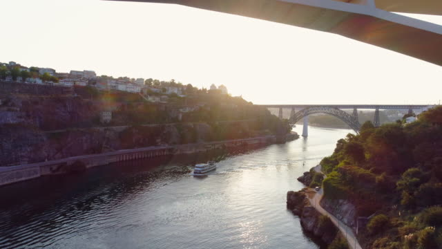 vídeos de stock e filmes b-roll de aerial shot above douro river in porto at sunrise - douro