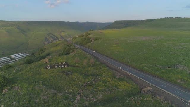 イスラエル北部のゴラン高原とタイベリア上空の空中撮影。ガリラヤ海の上の緑の風景や山々やヨルダン渓谷のキナートとオープンフィールドでロードレーンで運転車 - 陸の乗り物点の映像素材/bロール