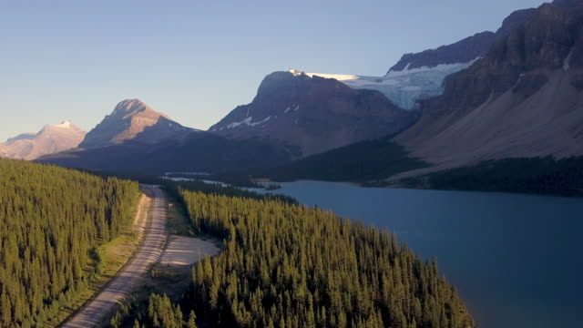 Aerial shot above lake and road with mountains in the background while sunset video