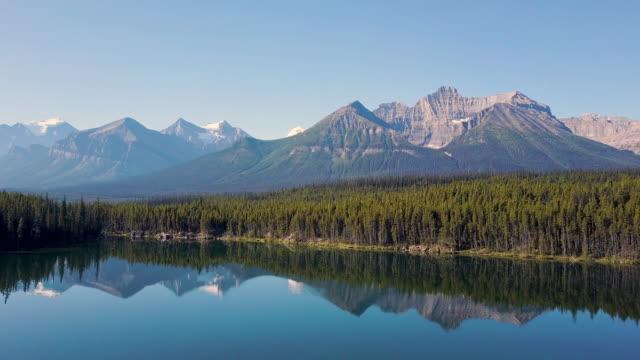 antenn skott ovanför sjön med reflektioner över bergen - klippiga bergen bildbanksvideor och videomaterial från bakom kulisserna