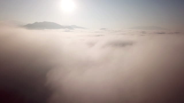 aerial shot above the clouds sunrise time in to the mist on the sky - d'atmosfera video stock e b–roll