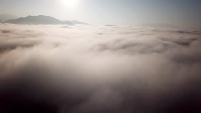 Aerial shot above the clouds sunrise time in to the mist on the sky Aerial shot above the clouds sunrise time in to the mist on the sky 4K(UHD) atmosphere stock videos & royalty-free footage