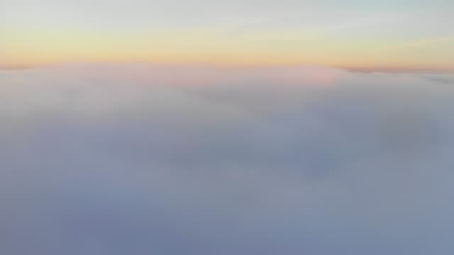aerial shot above thick clouds upper surface against horizon fantastic aerial shot above thick cumulus clouds boundless upper surface against pink horizon of blue sky atmosphere stock videos & royalty-free footage