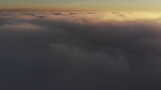 aerial shot above thick clouds upper surface against horizon