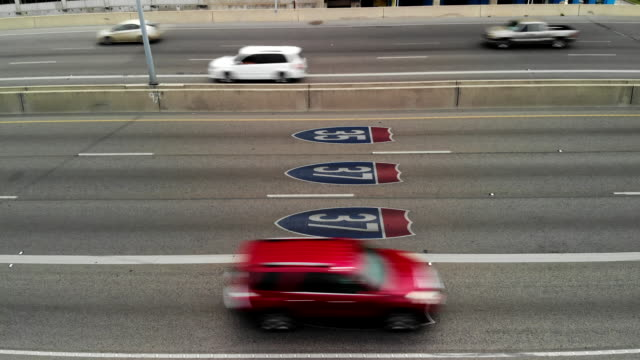 aerial shot ascending over the 281 freeway in san antonio with signs for the 35 and 37 freeways as cars pass - san antonio texas stock videos & royalty-free footage
