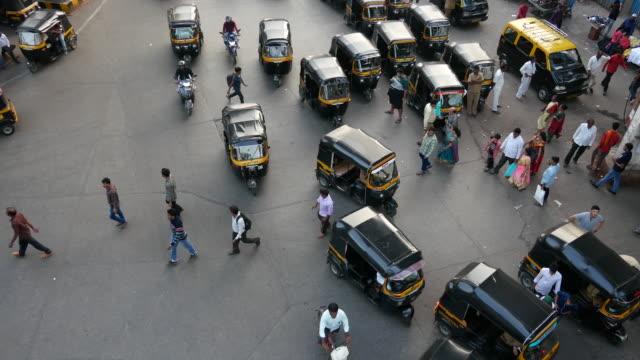 Aerial shot Auto Rickshaws and People in Mumbai, Andheri. Rickshaws and People on the road outside Andheri Railway Station, Mumbai. indian culture stock videos & royalty-free footage