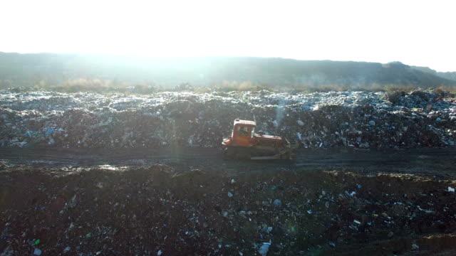 Aerial shot: bulldozer works with garbage at huge dump video