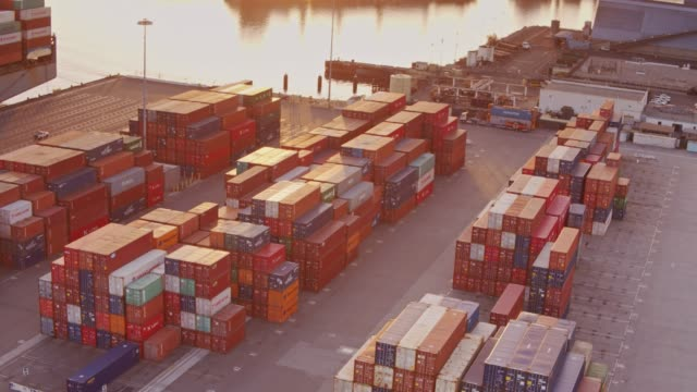 vídeos de stock e filmes b-roll de aerial shot circling over container yard with loaded cargo ship in dock - docas