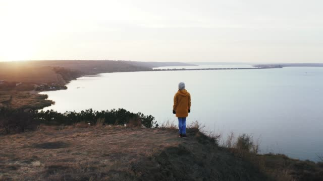 Aerial shot, drone flight around young adult woman in yellow coat that standing on cliff watching at sunset on sea, parallax 360 Aerial shot, drone flight around young adult woman in yellow coat that standing on cliff watching at sunset on sea, parallax 360 wide angle stock videos & royalty-free footage