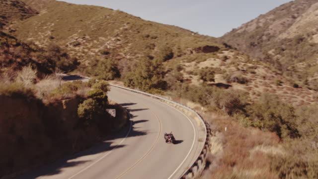 vidéos et rushes de aerial shot motocycliste extrême moto sport vélo sur route sinueuse filmée d'en haut - moto sport