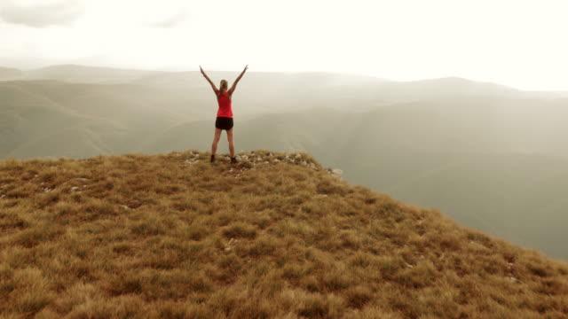 Aerial shot female runner on top of mountain raising hands video