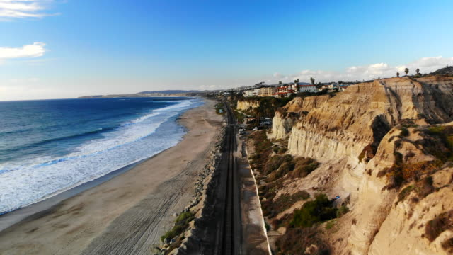 Aerial Shot Flying High Above the Beachside Train Tracks and Cliffs in San Clemente, California with Crashing Waves, and Beautiful Blue Skies