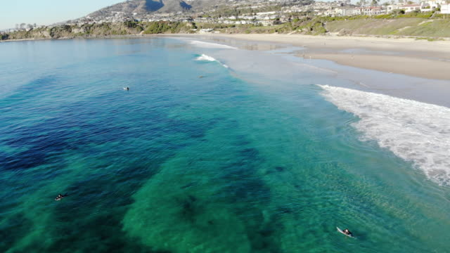 vídeos de stock e filmes b-roll de aerial shot flying in from the crystal clear ocean, past a group of surfers, to the sandy beach and cliffs in the distance at salt creek beach in laguna, orange county, california. - califórnia