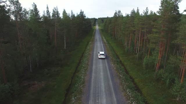 antenn skott efter bil körning på landsväg i skogen - pine forest sweden bildbanksvideor och videomaterial från bakom kulisserna