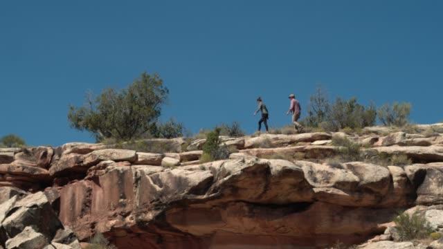 vídeos de stock, filmes e b-roll de aerial shot por baixo de duas pessoas andando em um aro rochoso do colorado monumento nacional no deserto de grand junction, colorado - penedo