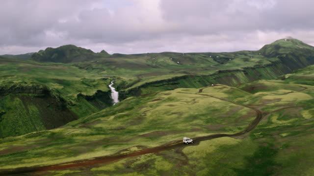 バック グラウンドで滝と山の道路上に 4 × 4 suv 車の空中ショット - 起伏の多い地形点の映像素材/bロール