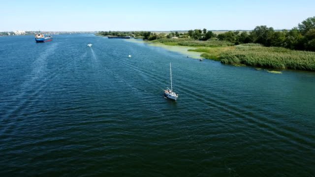 aerial shot of a beautifully moving yacht in the southern bug on a sunny day - pentola a vapore video stock e b–roll