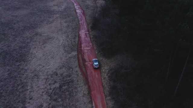 Aerial shot of a car driving on a dirt road