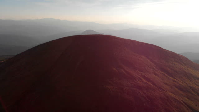Aerial shot of a Carpathian Mountain with people and a cross on its top