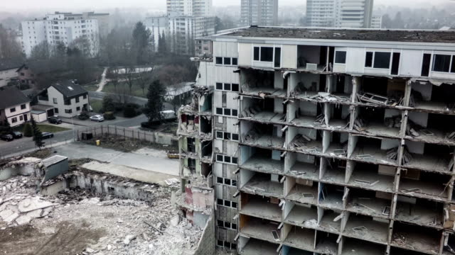 Aerial shot of a destroyed Building Aerial shot of demolished buildings. Can be used as war scene. Foggy grey weather supports depressive atmosphere. earthquake stock videos & royalty-free footage