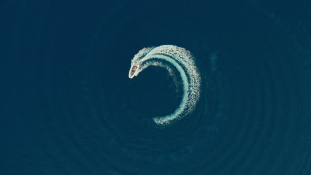 Aerial shot of a fast speedboat with a red roof top going around in the circle in a clear turquoise magical ocean.