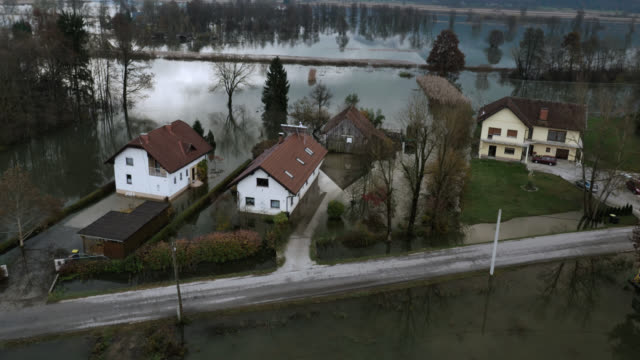 Aerial shot of a few houses surrounded by flood Aerial pan shot of few houses surrounded by the flood, caused by heavy rain, on a marsh in a 100 year floods in Ljubljana basin, Europe. slovenia stock videos & royalty-free footage