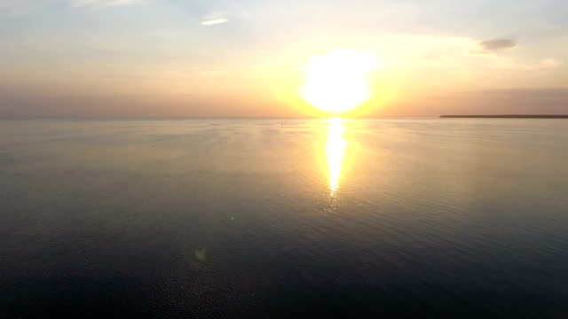 Aerial shot of a gleaming sunset over sparkling sea waters on a sunny day in summer video