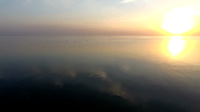 Aerial shot of a glowing sunset over shimmering sea waters on a sunny day in summer video