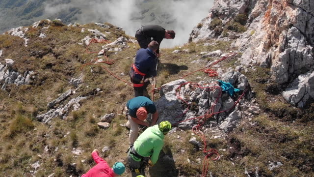Aerial shot of a group of climbers on top of a mountain pulling a rope.