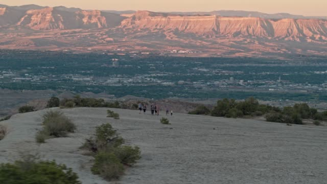 aerial shot of a group of thirty-something people hike together in the desert of the colorado national monument over grand junction, colorado overlooking the bookcliffs at sunset - колорадо стоковые видео и кадры b-roll