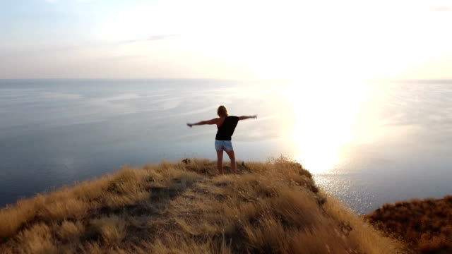 Aerial shot of a happy woman standing on a seacoast hill with sagebrush video