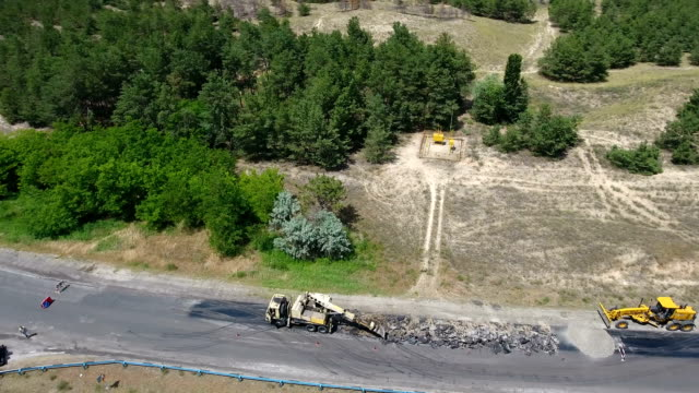 Aerial shot of a highway blacktopping, excavating, and repairing in summer An exciting bird`s eye view of a road repairing and blacktopping with an excavator breaking old asphalt, trucks and other vehicles standing nearby on a sunny day in summer. crane construction machinery stock videos & royalty-free footage