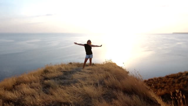 Aerial shot of a jolly woman standing on a seacoast hill with sagebrush video