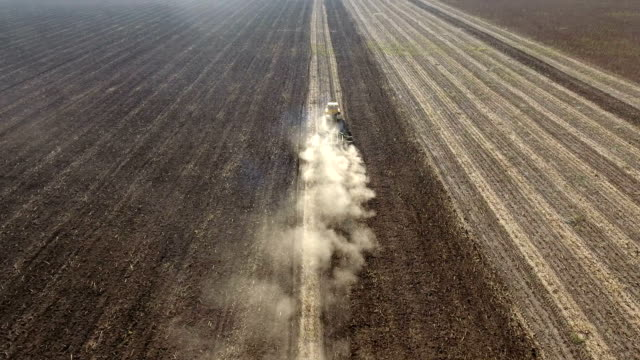 Aerial shot of a modern tractor which plows the agricultural field in spring video