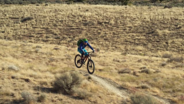 aerial shot of a mountain biker riding a desert trail on 18 road in fruita, colorado - bike tire tracks video stock e b–roll
