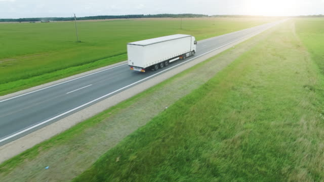 Video Aerial Shot of a Picturesque Highway Road and Trucks Driving on It.
