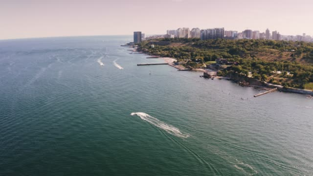 Aerial shot of a sea coast line during summer sunny day, boats are passing by