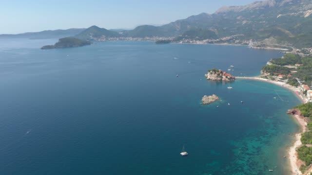 Aerial shot of a sea coast, small island in the sea and mountains