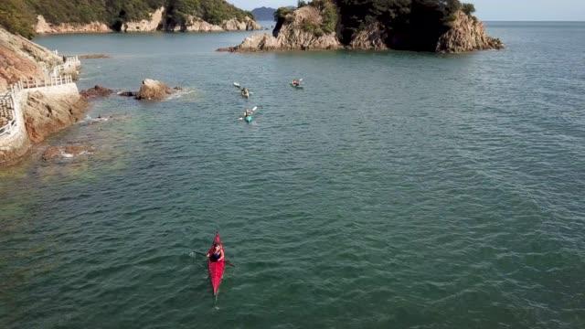 antenn skott av en liten grupp människor havskajak - stillsam scen bildbanksvideor och videomaterial från bakom kulisserna