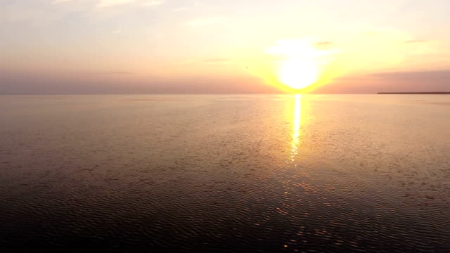 Aerial shot of a splendid sunset over sparkling sea waters on a sunny day in summer video