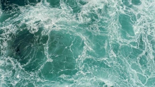 vídeos de stock e filmes b-roll de aerial shot of a turquoise ocean boiling with foamy storm waves.  4k, uhd - ferver