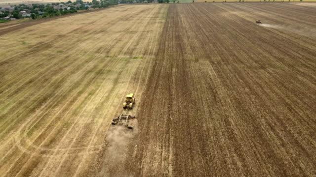 luftaufnahme von einem ukrainischen feld und einen großen traktor ziehen eine egge im sommer - aerial overview soil stock-videos und b-roll-filmmaterial