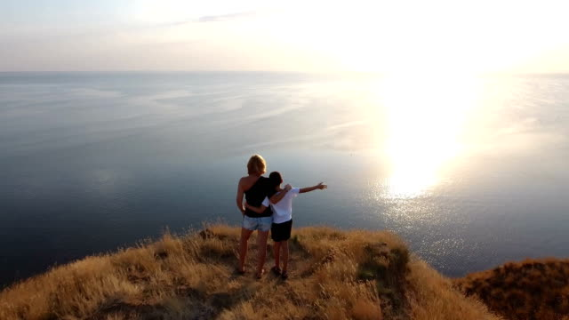 Aerial shot of a woman and her son standing on a seacoast hill with sagebrush video