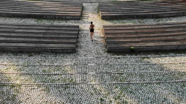 aerial shot of a woman running - ступеньки стоковые видео и кадры b-roll