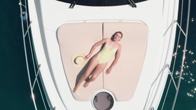 Aerial shot of a young woman relaxing and sunbathing on a yacht - boat that is parked at the marine. Aerial shot of a young woman relaxing and sunbathing on a yacht - boat that is parked at the marine. She puts a straw hat on her face. K4. Top travel destination. Vacation in Croatia. sunbathing stock videos & royalty-free footage