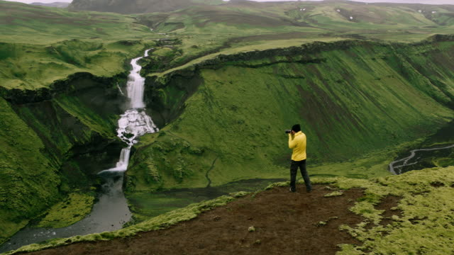 Aerial shot of adventure travel photographer standing on edge of cliff taking photos of waterfall mountain landscape