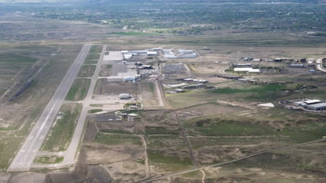 Aerial Shot of an Air Strip in Western Colorado The camera flies captures Walker Field Airport in Grand Junction, Colorado including its runway, the surrounding businesses, and the city of Grand Junction in the background. airfield stock videos & royalty-free footage