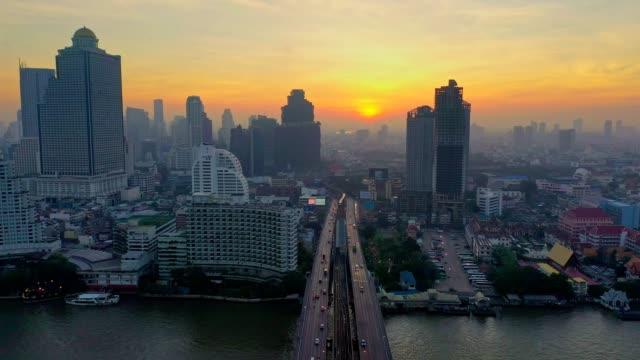 vídeos de stock, filmes e b-roll de foto aérea da cidade de bangkok, contra o rio chao phraya, bts sky trem e taksin ponte na estrada de charoen krung ao nascer do sol - multicóptero