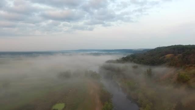 vídeos de stock, filmes e b-roll de tiro aéreo de belo ambiente rural no início da manhã. vista panorâmica incrível no vale da montanha com rio ao amanhecer. voando pelo largo prado com neblina. cena de natureza calma. câmera lenta - multicóptero